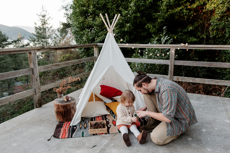 happy father playing with daughter near teepee tent